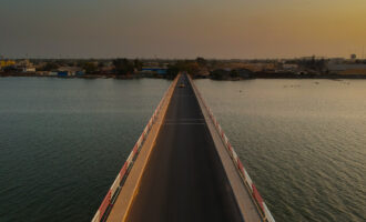 Aerial view of the road bridge over casamance river in Ziguinchor, Senegal, Africa during a sunset. Looking towards the city above the driving platform with yellow taxi crossing the bridge.
